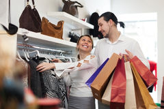 Young couple choosing clothes at shop Stock Photos