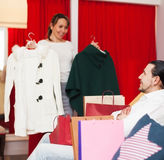 Young couple choosing coat at boutique Royalty Free Stock Images