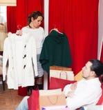 Young couple choosing coat at market Royalty Free Stock Photos