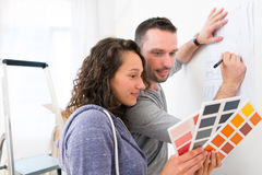 Young couple choosing colors of their new flat. View of a Young couple choosing colors of their new flat Stock Photos