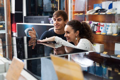 Young couple choosing kitchen stove. Young family choosing kitchen stove in hypermarket and smiling royalty free stock image