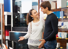 Young couple choosing kitchen stove. In hypermarket and smiling royalty free stock images