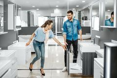 Couple chooosing new bathroom furniture in the shop. Young couple choosing new bathroom furniture at the plumbing shop with lots of sanitary goods royalty free stock photography
