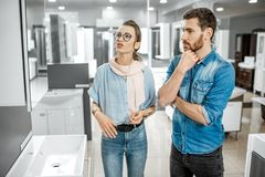 Couple chooosing new bathroom furniture in the shop. Young couple choosing new bathroom furniture at the plumbing shop with lots of sanitary goods royalty free stock image