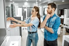 Couple chooosing new bathroom furniture in the shop. Young couple choosing new bathroom furniture at the plumbing shop with lots of sanitary goods stock image