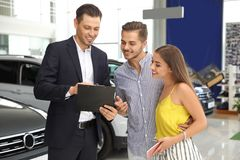 Young couple choosing new car with salesman. In salon royalty free stock photos