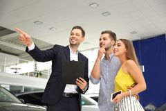 Young couple choosing new car with salesman. In salon stock photos