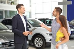 Young couple choosing new car with salesman. In salon stock image