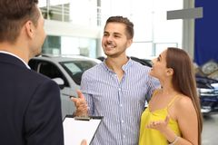 Young couple choosing new car with salesman. In salon royalty free stock images