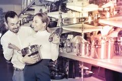 Young couple choosing new saucepan in dinnerware store Stock Photo