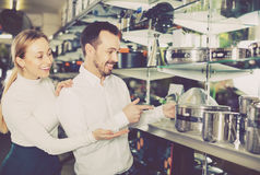 Young couple choosing new saucepan in dinnerware store Stock Photography