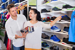Young couple choosing new sneakers in sports store royalty free stock photos