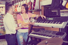 Young couple choosing synthesizer in music shop. Young couple choosing synthesizer in music instruments shop royalty free stock photography