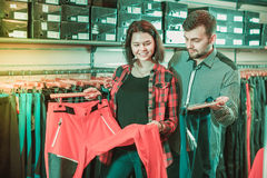 Young couple choosing touristic trousers in sports clothes store Royalty Free Stock Photos