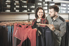 Young couple choosing touristic trousers in sports clothes store Stock Photos