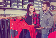 Young couple choosing touristic trousers in sports clothes store Stock Images