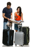 Young couple choosing travel destination. Young family going to vacations, choosing travel destination. Male and female standing with travel suitcases and Royalty Free Stock Images