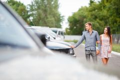 A young couple is choosing a used car. Used car theme. A young guy with a girl walks in the parking lot and chooses a car stock photo
