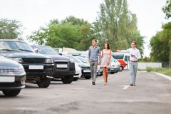 A young couple is choosing a used car. Used car theme. A young guy with a girl walks in the parking lot and chooses a car royalty free stock photo