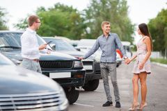 A young couple is choosing a used car. Used car theme. A young guy with a girl walks in the parking lot and chooses a car stock image