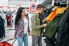 7f84f8da7a Young couple choosing warm clothes in supermarket royalty free stock  photography