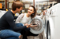 Young couple choosing washing machine. Happy european family couple buying new clothes washer in store stock image