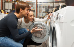 Young couple choosing washing machine. Positive couple buying new clothes washer in supermarket royalty free stock photo