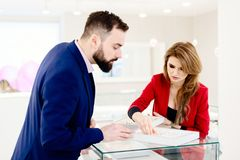 Young couple choosing wedding ring in jewelry store. Wedding decisions. Buying a present. Jewelry store. Attractive men with a beard choosing a ring gift in royalty free stock photo
