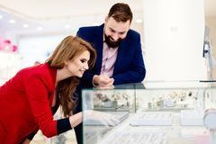 Young couple choosing wedding rings in jewelry store. Royalty Free Stock Images