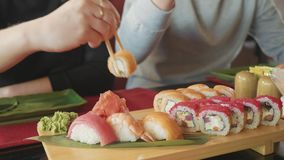 Young couple with chopsticks takes sushi from a plate in a japanese restaurant. stock footage