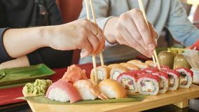 Young couple with chopsticks takes sushi from a plate in a japanese restaurant. Men and women starts eats japanese food. Focus on the seafood plate, close-up Royalty Free Stock Photo