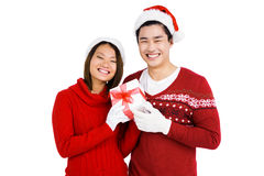 Young couple in christmas attire holding gift Stock Photos