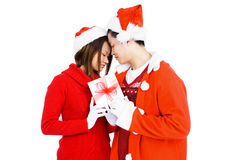 Young couple in christmas attire holding gift Royalty Free Stock Photos