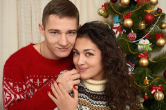 Young couple in christmas decoration. Home interior with gifts and fir tree. New year holiday concept. Love and tenderness. Royalty Free Stock Image