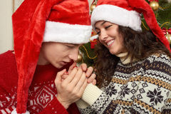 Young couple in christmas decoration. Man blowing warms on woman hands. Home interior with gifts and fir tree. New year holiday co Royalty Free Stock Images