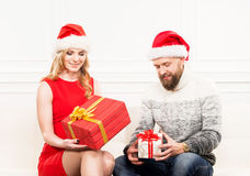 Young couple in Christmas hats holding presents Stock Photo