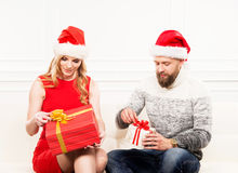 Young couple in Christmas hats holding presents Stock Photos