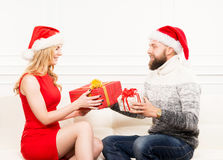 Young couple in Christmas hats holding presents Royalty Free Stock Image