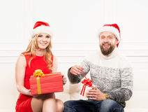 Young couple in Christmas hats holding presents Stock Images