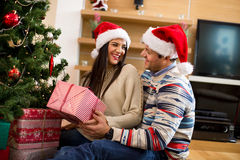 Young couple in Christmas hats holding presents Stock Image