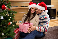 Young couple in Christmas hats holding presents Royalty Free Stock Photography