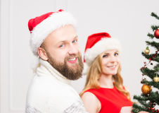 Young couple in Christmas hats next to a Christmas tree Royalty Free Stock Photography