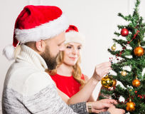 Young couple in Christmas hats next to a Christmas tree Stock Photos