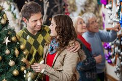 Young Couple In Christmas Store With Parents In Stock Photos