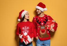 Young couple in Christmas sweaters and hats with gifts. On color background stock images