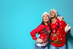 Young couple in Christmas sweaters and knitted hats on color background. Space for text royalty free stock photos