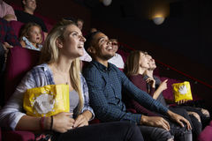 Young Couple In Cinema Watching Film And Eating Popcorn Royalty Free Stock Photos