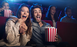 Young couple at the cinema watching an horror movie. Young scared couple at the cinema watching an horror movie and screaming, she is holding her boyfriend's Royalty Free Stock Images