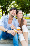 Young couple in city park drinking coffee Stock Image