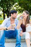 Young couple in city park drinking coffee Royalty Free Stock Images